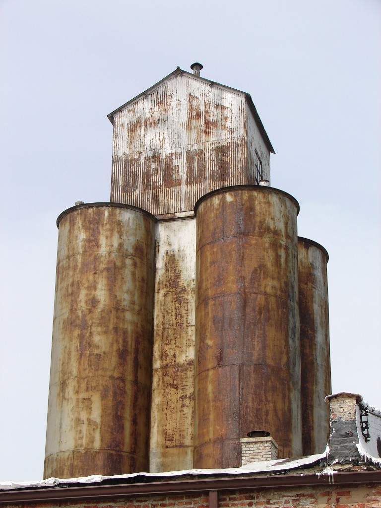 Four rusty grain elevators with house-shaped structure on top