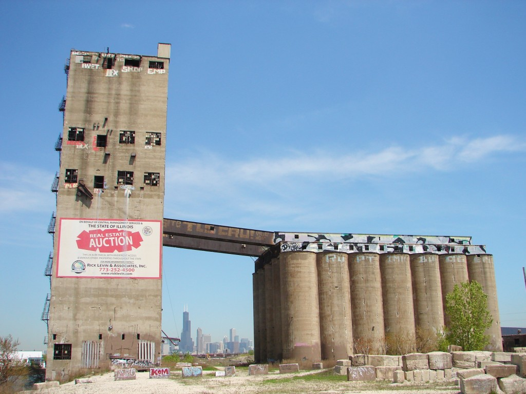 Santa Fe Grain Elevator in Chicago with downtown skyline show in the distance between structures, blue sky above